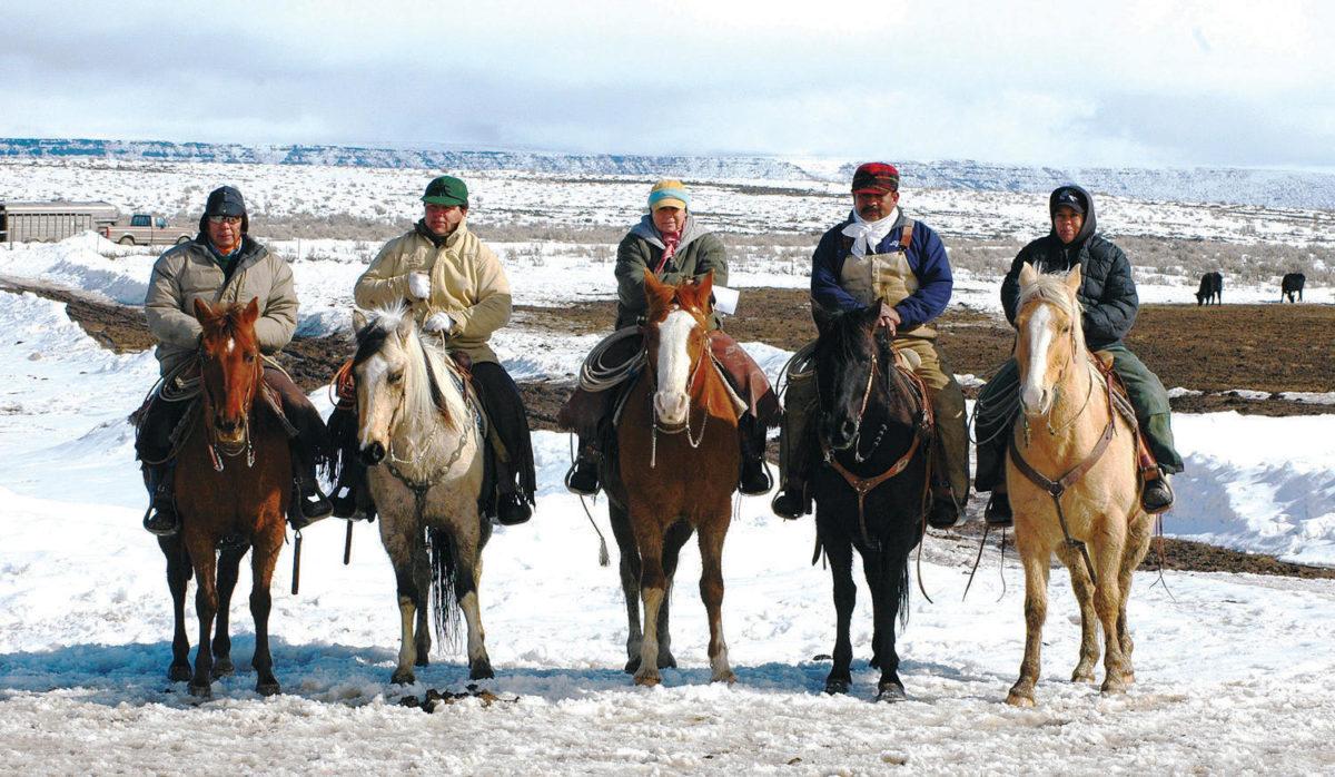 Five American Indians on horseback in a snowy rangeland